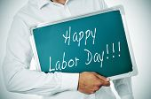 picture of labor  - a man holding a chalkboard with the sentence happy labor day written in it - JPG