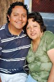 stock photo of older men  - Middle aged Hispanic mother hugs her grown son.