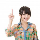 Young pretty asian woman pointing up. Isolated on the white background.
