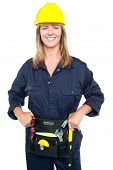 foto of jumpsuits  - Attractive confident female worker in jumpsuit holding tool belt wrapped around her waist - JPG