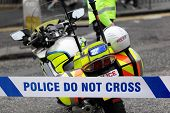stock photo of crime scene  - Policeman and police motorcycle behind cordon tape at an accident or crime scene - JPG