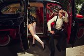 Young couple sitting  inside retro car