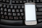 Smart Phone Over Black Keyboard