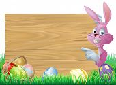 pic of peep  - A cartoon pink Easter bunny rabbit peeping round a sign in green spring field full of chocolate decorated eggs - JPG