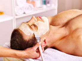 stock photo of beauty parlour  - Man with clay facial mask in beauty spa - JPG