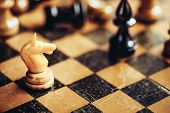 foto of chessboard  - White Chess Knight And Black Bishop Figures Standing On Chessboard - JPG