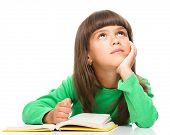 picture of daydreaming  - Young girl is daydreaming while reading book - JPG