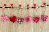 pic of pussy-willows  - Red heart shaped christmas decorations hanging on a pussy willow branch with pegs over old oak wood background - JPG