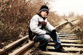 stock photo of sad boy  - Sad young boy sitting on abandoned place  - JPG