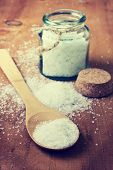 pic of sea salt  - wooden spoon with sea salt glass jar with salt on a wooden background in vintage style - JPG