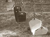 pic of swingset  - Sepia filter applied to retro swingset showing empty swings on playground - JPG