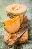 pic of cantaloupe  - Cantaloupe melon slices on olive wood cutting board - JPG