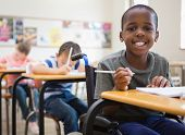 pic of pupils  - Disabled pupil smiling at camera in classroom at the elementary school - JPG