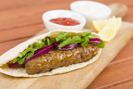 picture of raita  - Grilled minced meat kebabs in a flatbread with salad served with lemon wedges - JPG