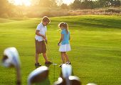 foto of golf bag  - Casual kids at a golf field holding golf clubs. Sunset ** Note: Visible grain at 100%, best at smaller sizes - JPG