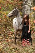 stock photo of appaloosa  - Beautiful girl with nice dress standing next to nice horse in autumn - JPG