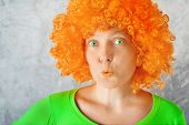 picture of character traits  - Beautiful young adult woman with orange wig and green eyes making kissing lips - JPG