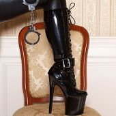 image of dominant woman  - Woman in latex boots step up to chair at vintage wall - JPG