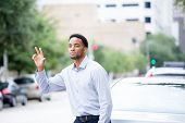 stock photo of say goodbye  - Closeup portrait young man in blue shirt raising hand to say hi goodbye or hitchhike flag or hail a cab isolated road and cars background outdoors - JPG