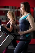 foto of cardio  - Sporty girl in sportswear running on cardio trainer treadmill in gym  - JPG