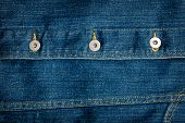 stock photo of denim jeans  - Worn blue crumpled denim jeans texture with some buttons - JPG
