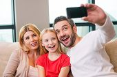 foto of family bonding  - Happy family of three bonding to each other and smiling while father photographing them with smart phone - JPG
