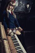 stock photo of lolita  - Schoolgirl with skull sitting on the old piano - JPG