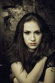 stock photo of gothic female  - Pretty gothic girl with black eyes over grunged background - JPG