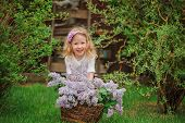 stock photo of headband  - horizontal portrait of cute child girl in flower headband playing in spring garden with basket of lilacs - JPG