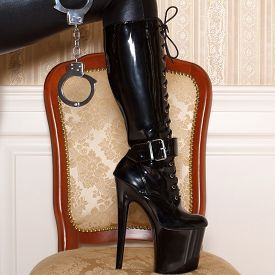 pic of sadism  - Woman in latex boots step up to chair at vintage wall - JPG