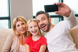 picture of bonding  - Happy family of three bonding to each other and smiling while father photographing them with smart phone - JPG