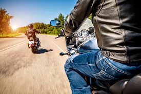 pic of biker  - Bikers driving a motorcycle rides along the asphalt road  - JPG