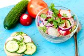 picture of chinese parsley  - Spring salad with radishes cucumber Chinese cabbage and red onion closeup vsteklyannoy bowl on a blue wooden background - JPG