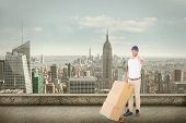 foto of trolley  - Happy delivery man pushing trolley of boxes against cityscape - JPG