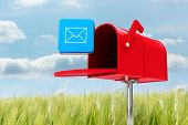 stock photo of postbox  - Red email postbox against green meadow - JPG