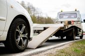 picture of accident emergency  - Loading broken car on a tow truck on a roadside  - JPG