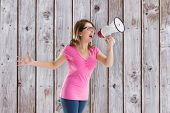 image of unnerving  - Angry woman with megaphone and glasses against wooden planks - JPG