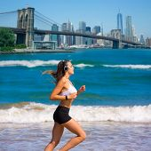 stock photo of brooklyn bridge  - Brunette girl running in New York Brooklyn bridge photo mount - JPG