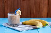 stock photo of banana  - Healthy homemade Chocolate banana smoothie in glass and fresh bananas on wooden background - JPG