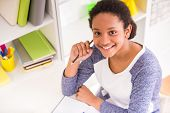 stock photo of mulatto  - Young pretty smiling mulatto schoolgirl sitting at the table and holding a pencil in hand on colorful background - JPG