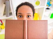 stock photo of mulatto  - Young pretty mulatto schoolgirl holding a book on colorful background - JPG