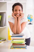 stock photo of schoolgirl  - Young pretty smiling schoolgirl sitting at the table and writing homework on colorful background - JPG
