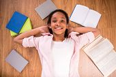 stock photo of mulatto  - Young smiling mulatto schoolgirl laying on the floor with some color books - JPG