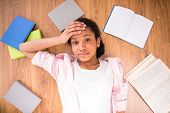 foto of mulatto  - Young tired mulatto schoolgirl laying on the floor with some color books - JPG