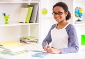 image of mulatto  - Young mulatto schoolgirl in glasses sitting at the table and writing homework on colorful background - JPG