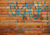 stock photo of paint spray  - Red brick wall with a graffiti of the drug related word CRACK written in blue spray paint