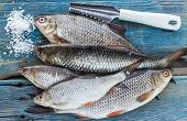 stock photo of caught  - Freshly caught fish on a wooden table and a knife for cleaning of scales - JPG