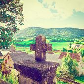 stock photo of french culture  - Stone Cross on the Background of the French Town Vintage Style Toned Picture - JPG