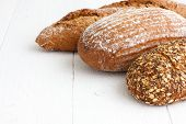 picture of whole-grain  - Mixed whole grain health breads on rustic white painted wood - JPG