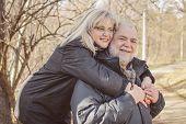stock photo of piggyback ride  - Happy Senior Man giving Mature Woman Piggyback ride outdoors - JPG